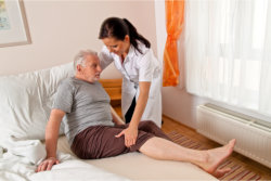 The caregiver helps the old man to lay down properly